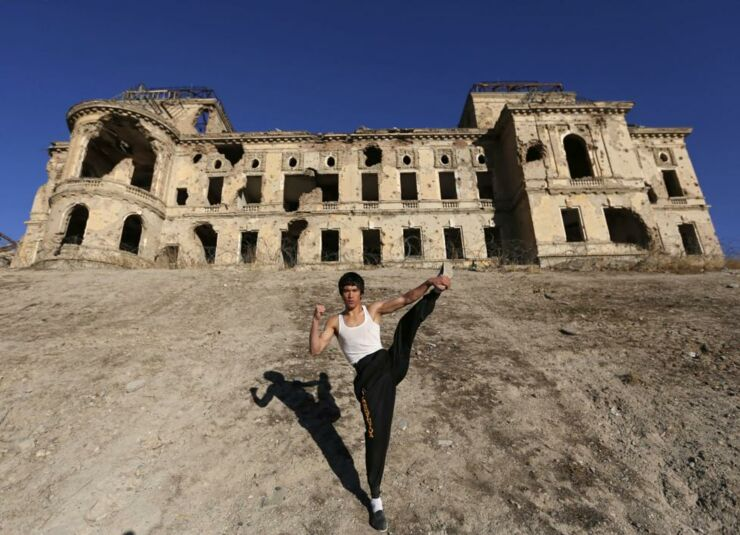 Abbas Alizada, who calls himself the Afghan Bruce Lee, poses for the media in front of the destroyed Darul Aman Palace in Kabul.