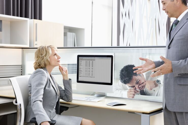Businessman explaining to manager in office --- Image by © Ocean/Corbis