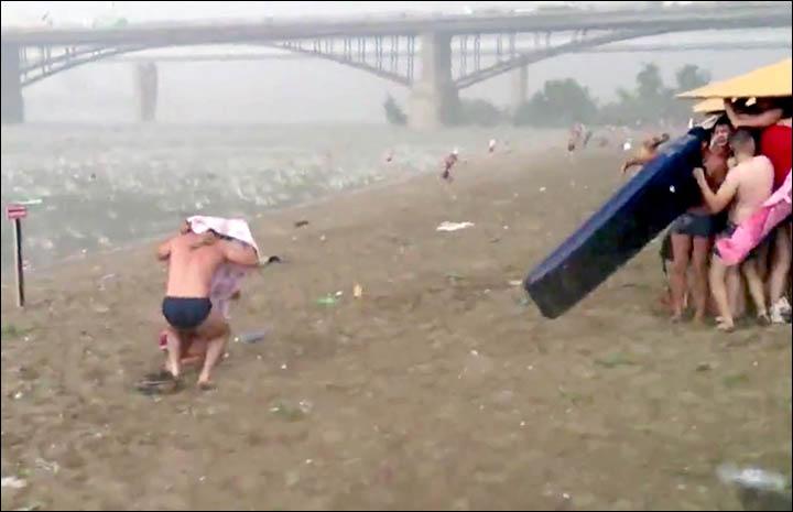 inside man under towel and people under umbrella